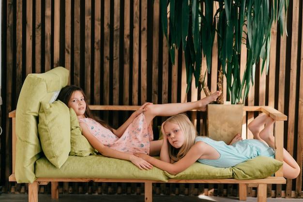 Zwei schöne modellmädchen in den bunten kleidern, die auf sofa in der terrasse liegen