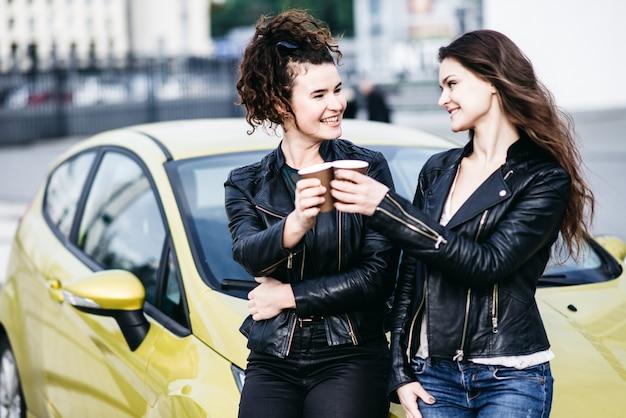 Zwei schöne moderne mädchen stehen am auto und haben spaß