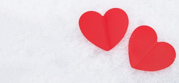 Zwei schöne romantische rote herzen zusammen auf einer weißen schneebedeckten wand. das konzept der liebe und des valentinstags.