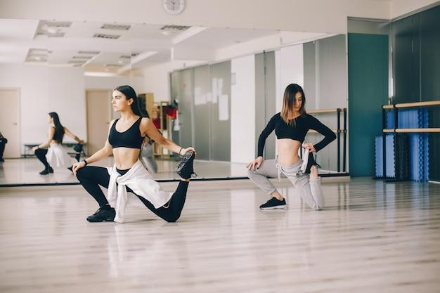 Zwei schöne schlanke mädchen tanzen und gymnastik in der tanzhalle