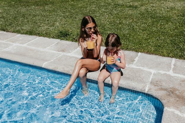 Zwei schöne schwesterkinder am pool gesunden orangensaft trinkend und spaß draußen habend. sommer und lifestyle-konzept
