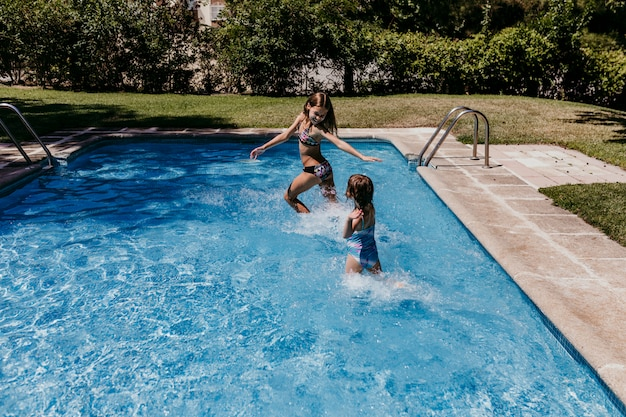 Zwei schöne schwesterkinder am pool spielen, laufen und haben spaß im freien. sommer- und lifestyle-konzept