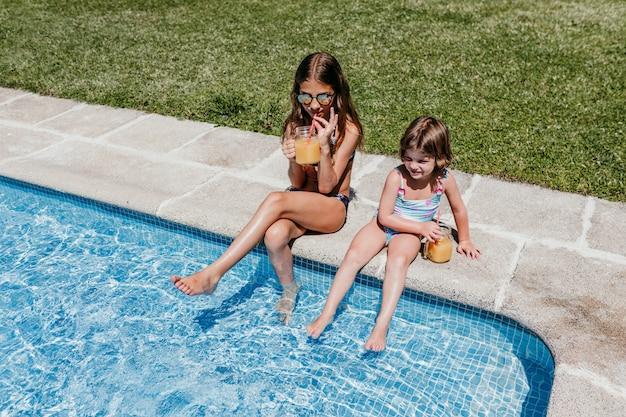 Zwei schöne schwesterkinder am pool trinken gesunden orangensaft und haben spaß im freien. sommer- und lifestyle-konzept