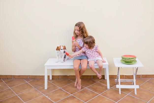 Zwei schöne schwesterkinder, die eine wassermeloneneiscreme mit ihrem netten hund essen. familienliebe und lebensstil im freien