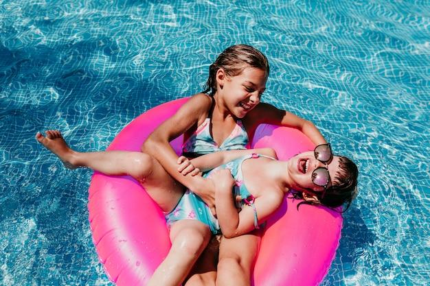 Zwei schöne schwestern, die auf rosa schaumgummiringe in einem pool schwimmen. kitzeln und lächeln.