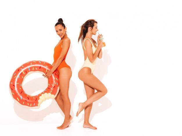 Zwei schöne sexy lächelnde frauen in den bunten badebekleidungsbadeanzügen des sommers. mädchen isoliert. lustige modelle, die neues cocktail smoozy getränk mit aufblasbarer matratze des donuts lilo trinken