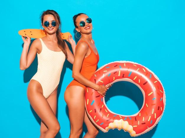 Zwei schöne sexy lächelnde frauen in den bunten badebekleidungsbadeanzügen des sommers. mädchen mit sonnenbrille. positive modelle, die spaß mit bunten penny-skateboards haben. mit donut lilo luftmatratze