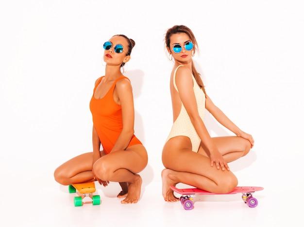 Zwei schöne sexy lächelnde frauen in den bunten badebekleidungsbadeanzügen des sommers. trendy girls in sonnenbrillen. positive modelle, die auf dem boden mit bunten penny-skateboards sitzen. isoliert