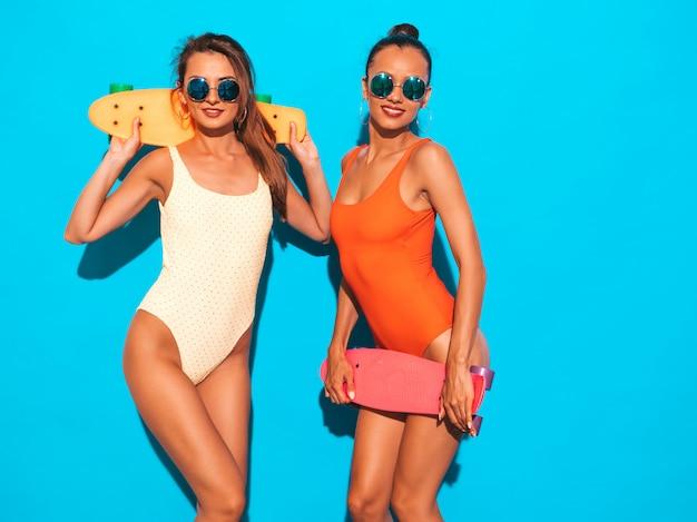 Zwei schöne sexy lächelnde frauen in den bunten badebekleidungsbadeanzügen des sommers. trendy girls in sonnenbrillen. positive modelle, die spaß mit bunten penny-skateboards haben. isoliert