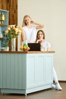 Zwei schöne studenten, die eine videokonferenz machen, die in der küche sitzt