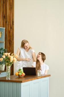 Zwei schöne studenten, die videokonferenz machen, die in der küche sitzt