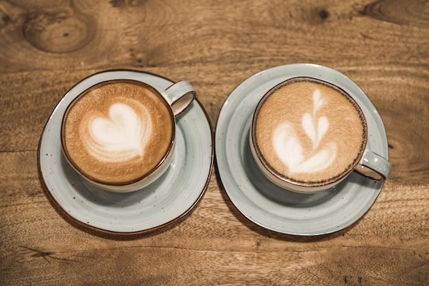 Zwei schöne tassen kaffee mit einer herzform auf einem hölzernen hintergrund. valentinstag konzept. selektiver fokus.