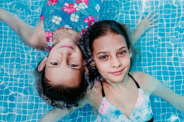 Zwei schöne teenager-mädchen, die in einem pool schweben und die kamera betrachten. spaß und sommerlicher lebensstil
