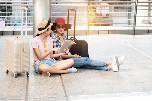 Zwei schöne touristen stehen im gespräch karte.