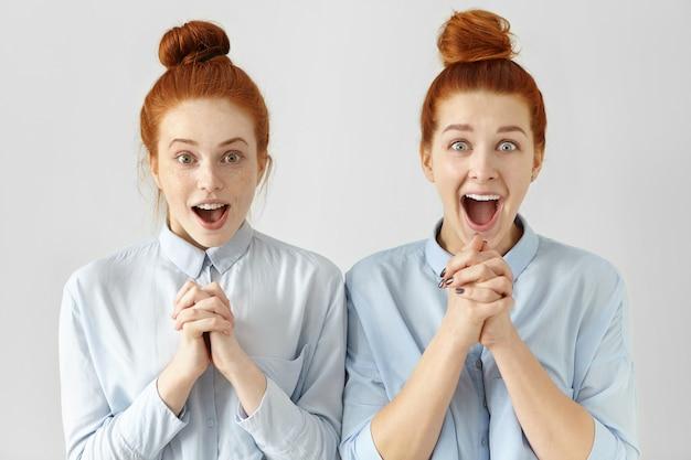 Zwei schöne überraschte arbeiterinnen mit ingwerhaar, gekleidet in die gleichen hemden