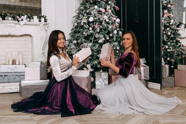 Zwei schöne und elegante frauen glücklich und lächelnd. geben sie einander weihnachtsgeschenke vor dem weihnachtsbaum