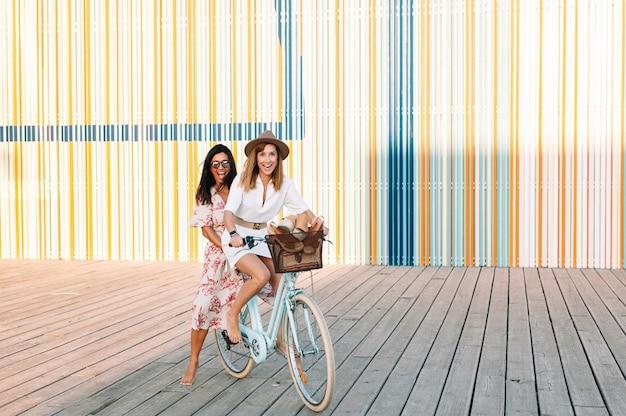 Zwei schöne und fröhliche erwachsene junge frauen genießen eine radtour in der sonnigen städtischen outdoor-freizeitaktivität
