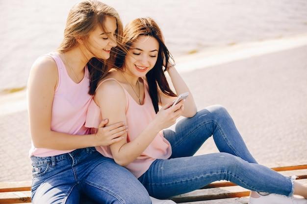Zwei schöne und helle freunde in den rosa t-shirts und in den blue jeans, die in der sonnigen stadt sitzen