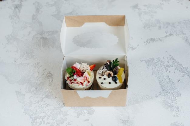 Zwei schöne und köstliche kleinigkeiten kuchen nahaufnahme auf einem hellen hintergrund in einer geschenkbox. dessert, gesundes essen.