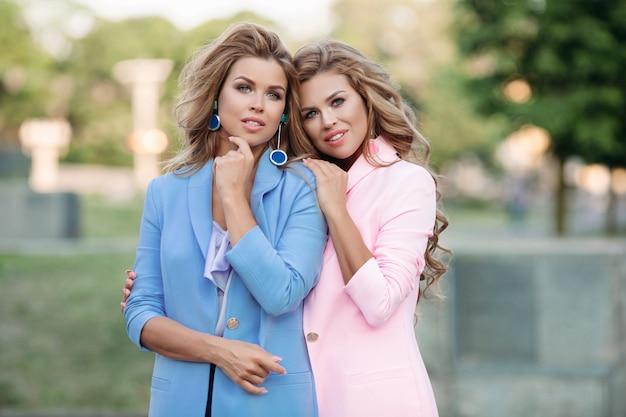 Zwei schöne und modische frauen in stilvollen rosa und blauen jacken