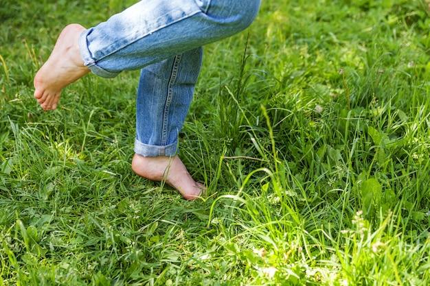 Zwei schöne weibliche füße, die auf gras im sonnigen sommermorgen gehen