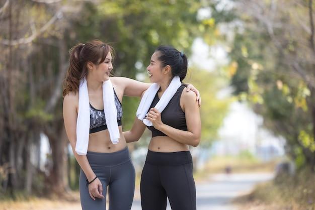Zwei schöne weibliche jogger, freundinnen, die sich im park ausdehnen