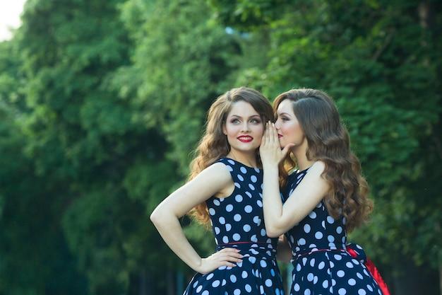 Zwei schöne zwillinge in gefleckten kleidern