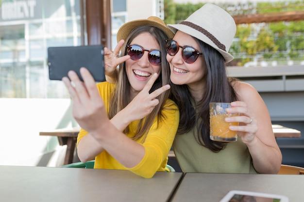 Zwei schönheiten, die in einem restaurant frühstücken und ein selfie mit handy nehmen. sie lachen. drinnen lifestyle und freundschaftskonzept