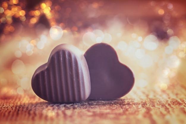 Zwei schokoladen-herzen auf einem hölzernen hintergrund, valentinsgrußtag.