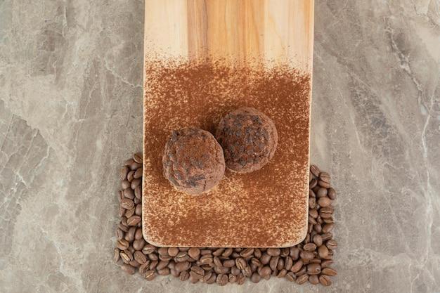 Zwei schokoladenplätzchen auf holzteller mit kaffeebohnen
