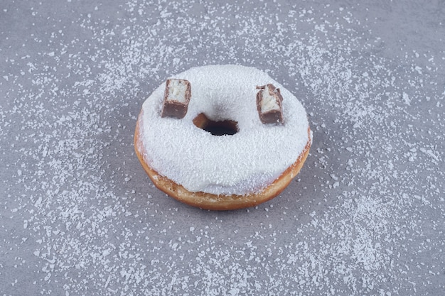 Zwei schokoladenstücke auf einem donut auf marmoroberfläche
