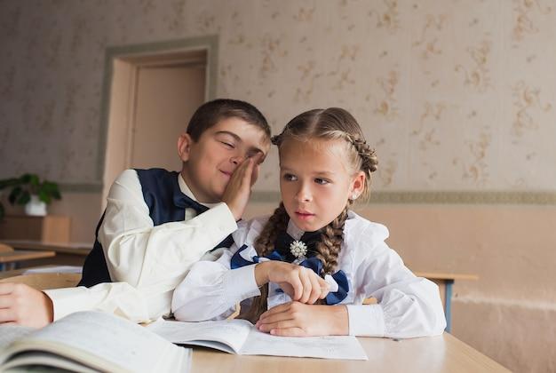 Zwei schüler, ein junge und ein mädchen, sitzen in der schule an einem schreibtisch und kommunizieren im ohr miteinander.