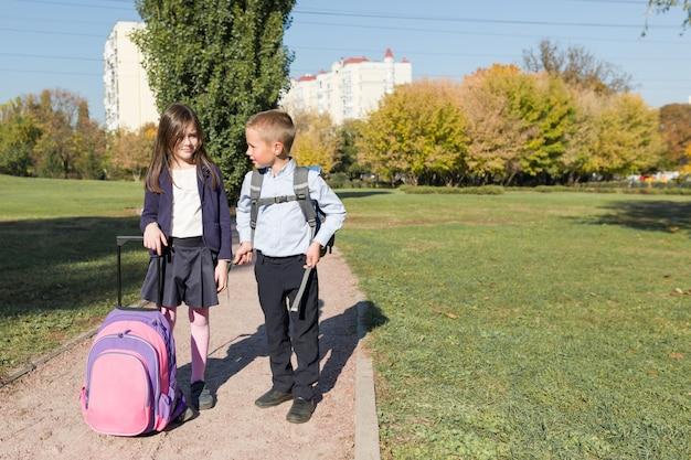 Zwei schüler jungen und mädchen mit rucksäcken gehen zur schule