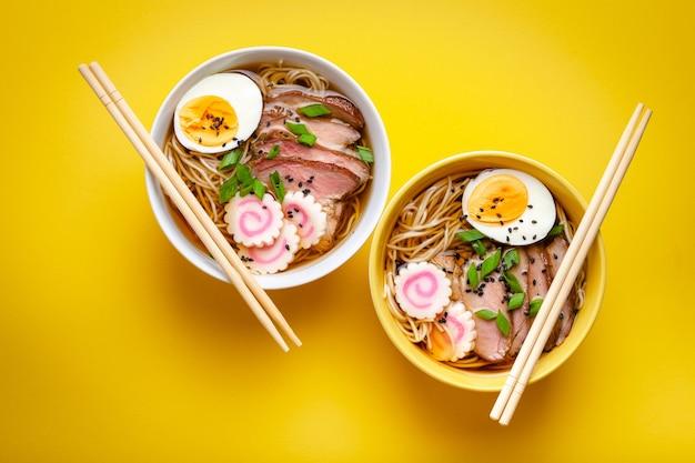 Zwei schüsseln japanische nudelsuppe ramen mit fleischbrühe, geschnittenem schweinefleisch, narutomaki, ei mit eigelb auf pastellgelbem hintergrund. traditionelles japanisches gericht, draufsicht, nahaufnahme, konzept,