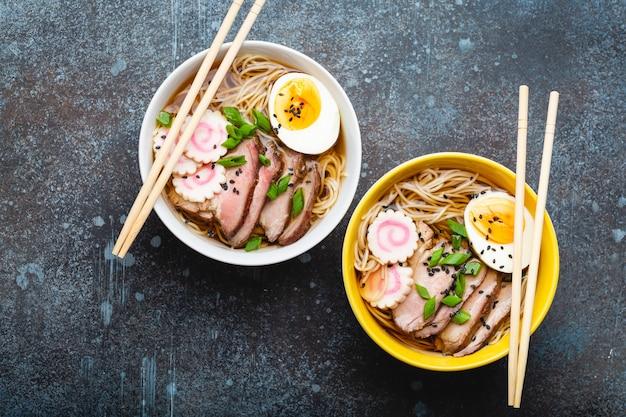 Zwei schüsseln japanische nudelsuppe ramen mit fleischbrühe, geschnittenem schweinefleisch, narutomaki, ei mit eigelb auf rustikalem steinhintergrund. traditionelles japanisches gericht, draufsicht, nahaufnahme, konzept,