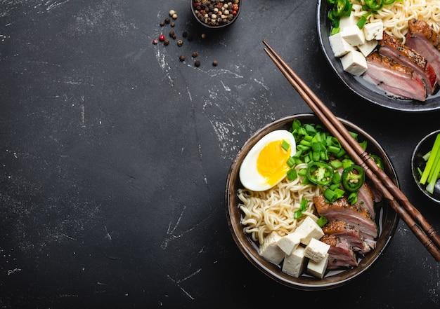 Zwei schüsseln leckere asiatische nudelsuppe ramen mit brühe, tofu, schweinefleisch, ei auf schwarzem rustikalem steinhintergrund, platz für text, nahaufnahme, draufsicht. heiße leckere japanische ramen-suppe zum abendessen mit kopierraum