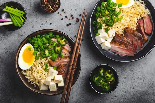 Zwei schüsseln leckere asiatische nudelsuppe ramen mit fleischbrühe, tofu, schweinefleisch, ei mit eigelb auf grauem rustikalem betonhintergrund, nahaufnahme, draufsicht. heiße leckere japanische ramensuppe zum abendessen nach asiatischer art