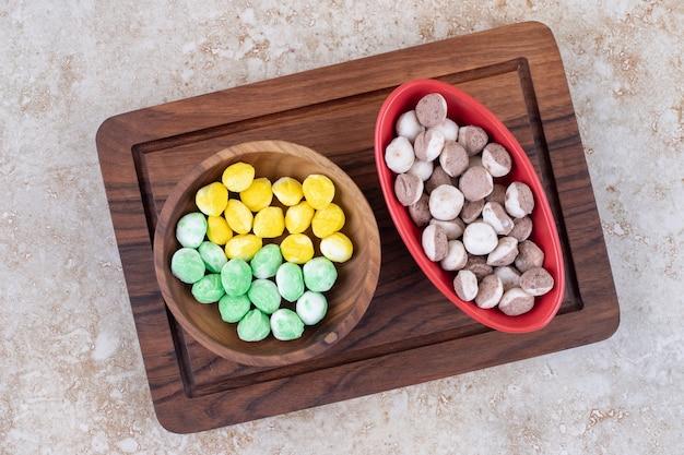 Zwei schüsseln mit bunten bonbons auf holzbrett