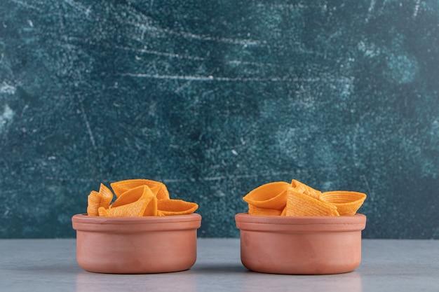Zwei schüsseln mit dreieckigen knusprigen chips auf steinhintergrund.