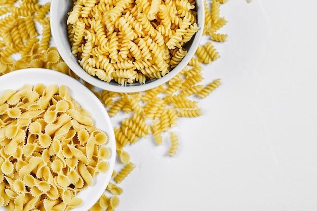 Zwei schüsseln mit ungekochter pasta auf weißem hintergrund