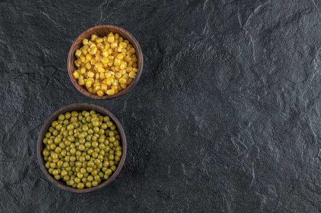 Zwei schüsseln voll mit grünen erbsen und maissamen