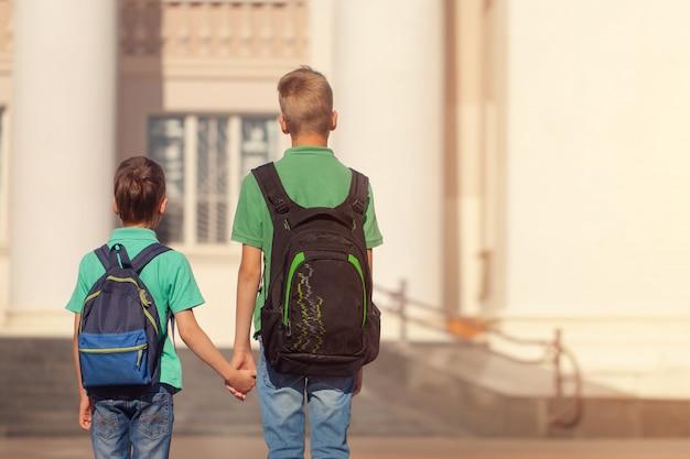 Zwei schulbrüder mit rucksack am sonnigen tag. glückliche kinder gehen zur schule. rückansicht