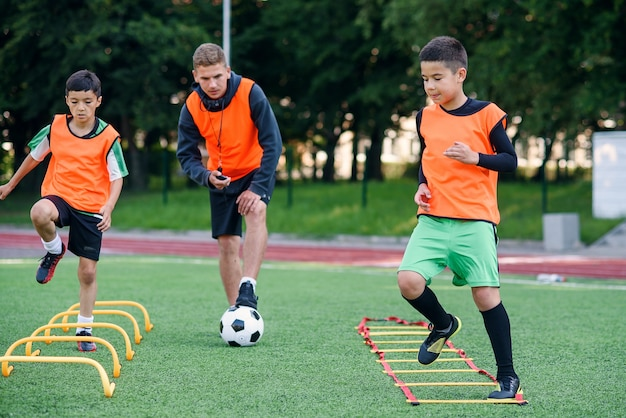 Zwei schuljungen führen während des fußball-sommercamps leiterübungen auf dem rasen durch. intensives fußballtraining mit dem trainer.