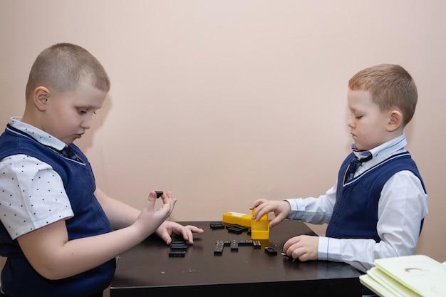 Zwei schulkinder spielen in der pause domino am tisch