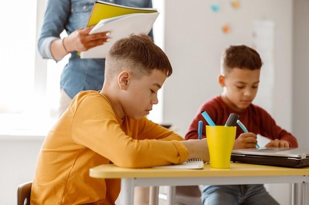Zwei schulkinder während einer unterrichtsstunde und einer prüfung in der schule