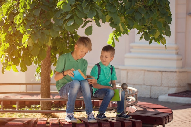 Zwei schulkinderjungen, die unter einem baum sitzen und bücher an einem sonnigen sommertag lesen