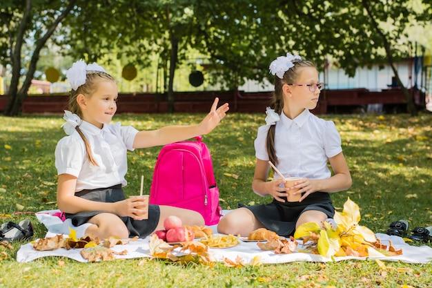 Zwei schulmädchen picknicken auf einer decke und winken freunden in einem sonnigen herbstpark zu. outdoor-erziehung für kinder. zurück zum schulkonzept