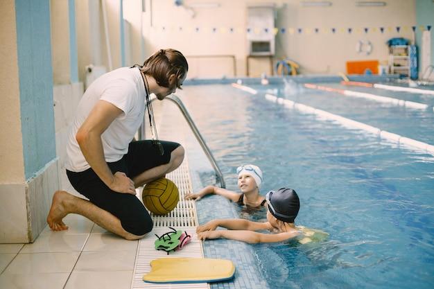 Zwei schulmädchen-wasserballspieler hören lehrer am pool. viel spaß, spielen und planschen in einem blauen schwimmbad