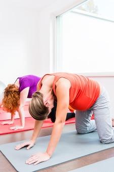 Zwei schwangere frauen, die während der pränatalen klasse trainieren