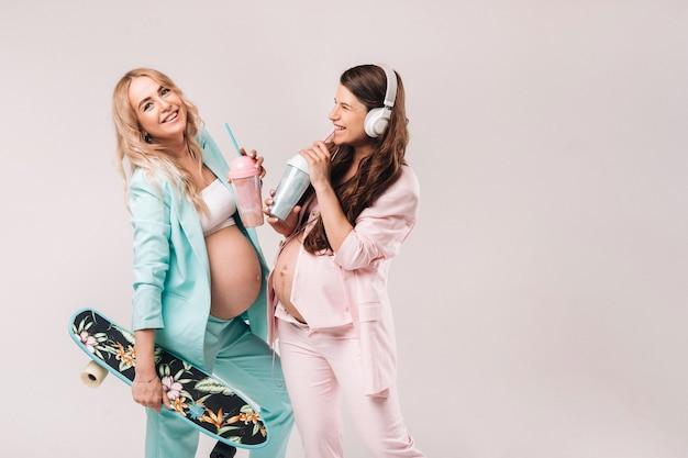 Zwei schwangere mädchen in türkisfarbenen und rosafarbenen anzügen mit saftgläsern, einem schlittschuh und kopfhörern stehen auf grauem hintergrund.